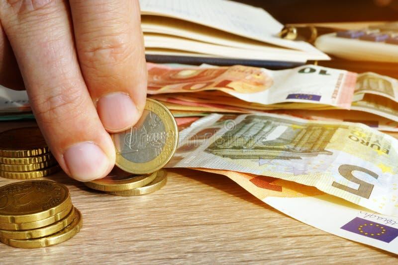 供以人员拿着欧洲硬币和钞票在书桌上 储蓄 图库摄影