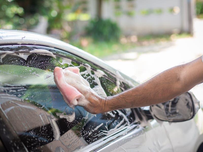 供以人员拿着海绵的手摩擦汽车用泡沫 洗车骗局 库存图片