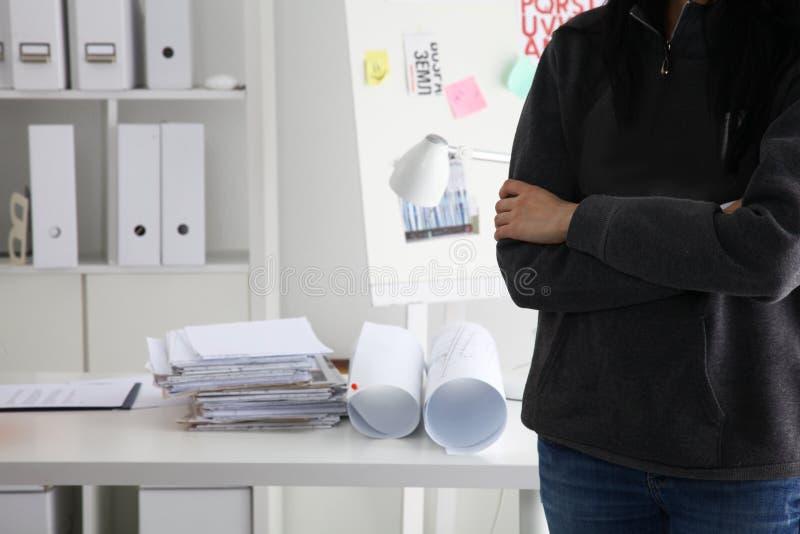 供以人员拿着盔甲的建筑师工程师佩带的衣服,站立在办公室 免版税库存照片