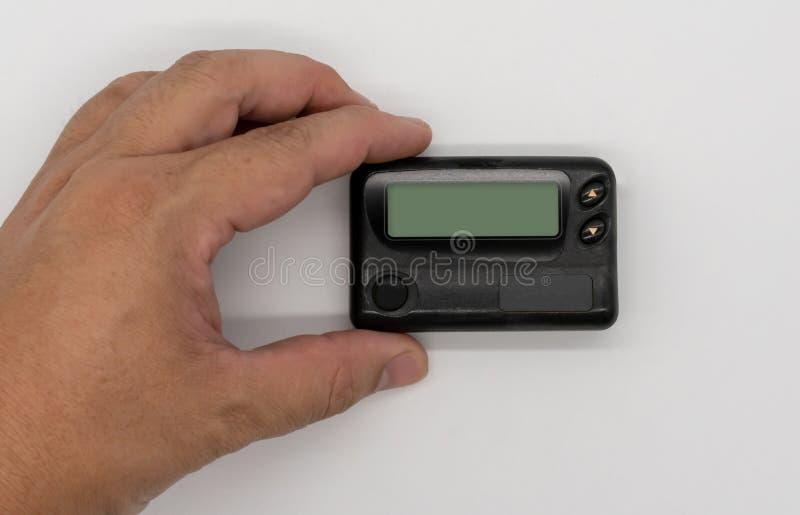 供以人员拿着通信传呼器的手葡萄酒小配件 免版税库存图片