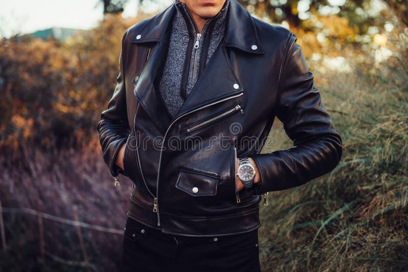 供以人员摆在佩带的黑的皮夹克和的手表户外 免版税库存图片