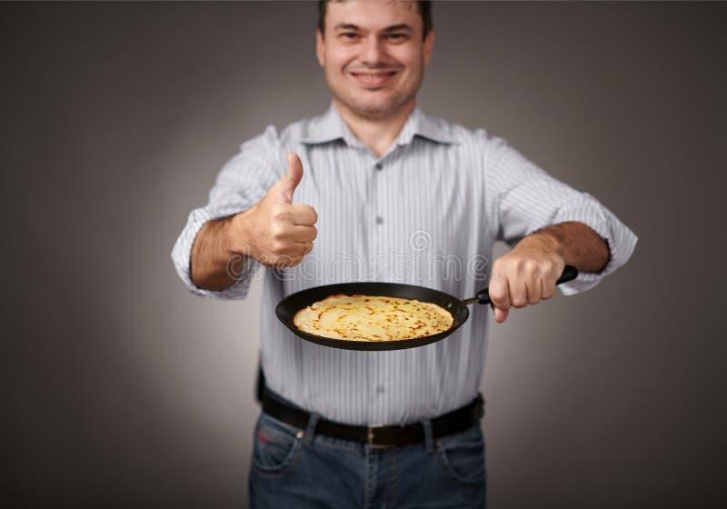 供以人员摆在用在平底锅的一个薄煎饼、白色衬衣和裤子、灰色背景、浅景深,锋利的薄煎饼和被弄脏的面孔 库存照片