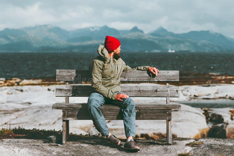 供以人员放松在享用海的长凳,并且山使旅行生活方式概念斯堪的纳维亚人环境美化 库存照片