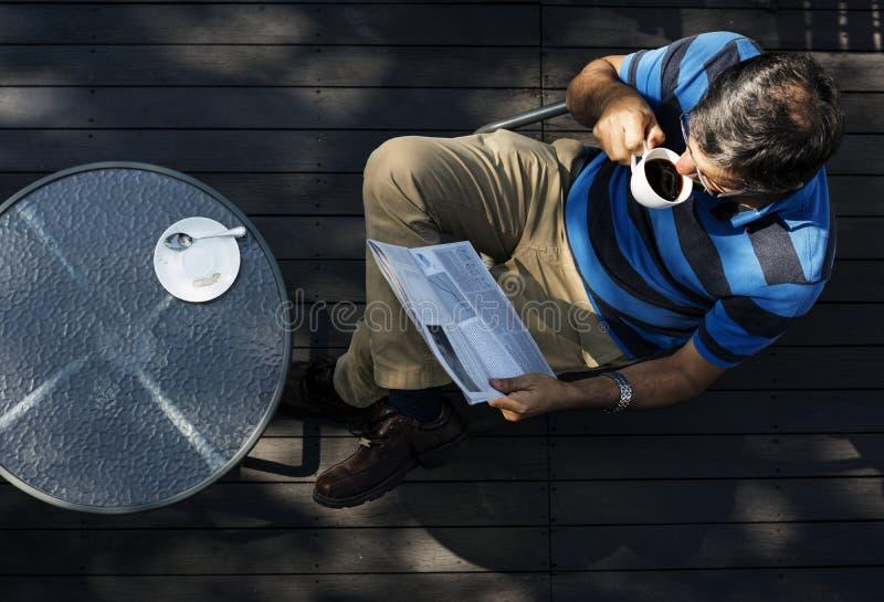 供以人员放松,当读报纸和喝咖啡时 免版税库存图片