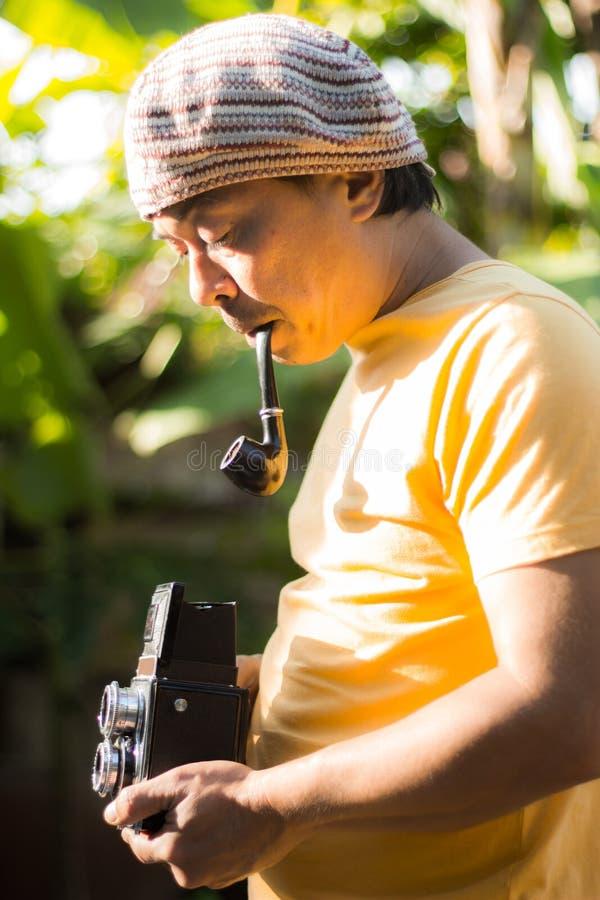 供以人员有老葡萄酒照相机的烟斗在手上 葡萄酒传统化了人摄影师照片有老照相机的 图库摄影