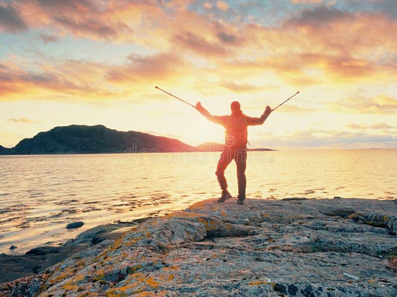 供以人员有背包和medicin拐杖的游人在多岩石的海滩 远足者享用空的岸 免版税库存照片