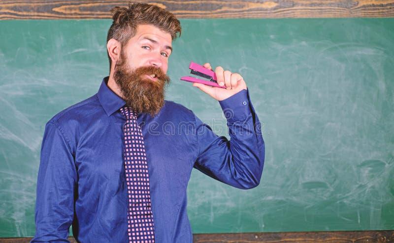 供以人员有胡子的老师或教育家在礼服举行订书机黑板背景中 学校用品和文具 使用 库存图片
