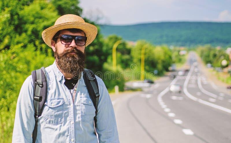 供以人员有胡子的行家背包徒步旅行者在高速公路边缘  我采取您 旅客等待的汽车无论如何把他带  库存图片