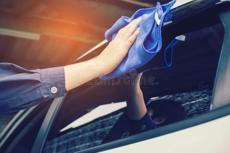 供以人员有microfiber布料白色汽车的清洁汽车 免版税库存照片