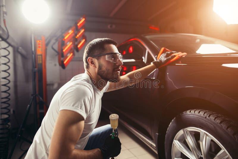 供以人员有microfiber布料,汽车详述的或valeting的概念的清洁汽车 免版税库存照片