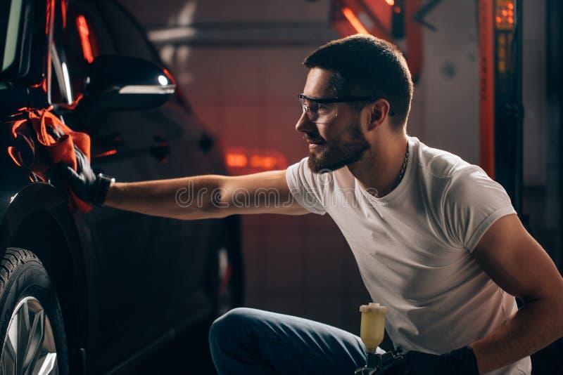 供以人员有microfiber布料,汽车详述的或valeting的概念的清洁汽车 库存图片