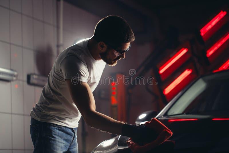供以人员有microfiber布料,汽车详述的或valeting的概念的清洁汽车 免版税库存图片