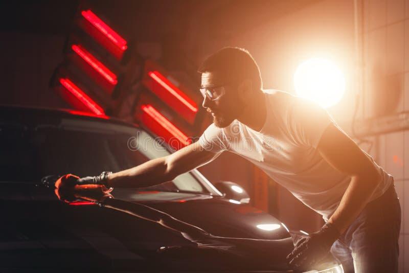 供以人员有microfiber布料,汽车详述的或valeting的概念的清洁汽车 库存照片
