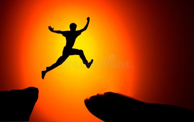 供以人员横跨从一个岩石的空白紧贴的跳跃对其他 供以人员跳过与空白的岩石在日落火热的背景 库存照片