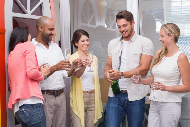 供以人员流行的瓶与他的队的香槟 库存照片