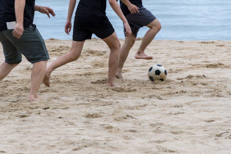 供以人员演奏在海滩的在沙子的足球和脚印 免版税库存照片