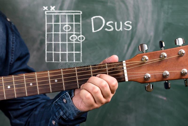 供以人员演奏在黑板显示的吉他弦,弦Dsus 免版税库存照片