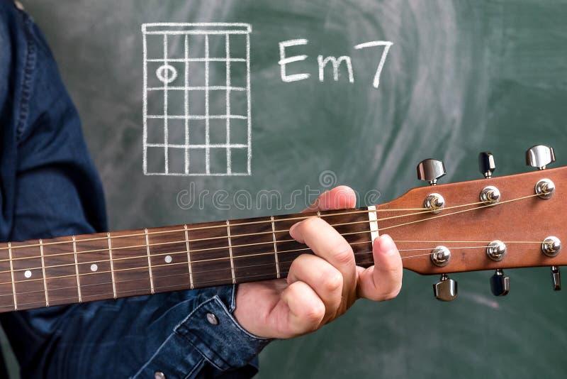 供以人员演奏在黑板显示的吉他弦,弦Em7 免版税库存图片