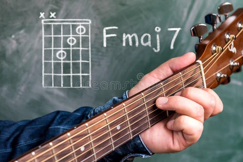 供以人员演奏在黑板显示的吉他弦,弦F 7少校 免版税库存图片