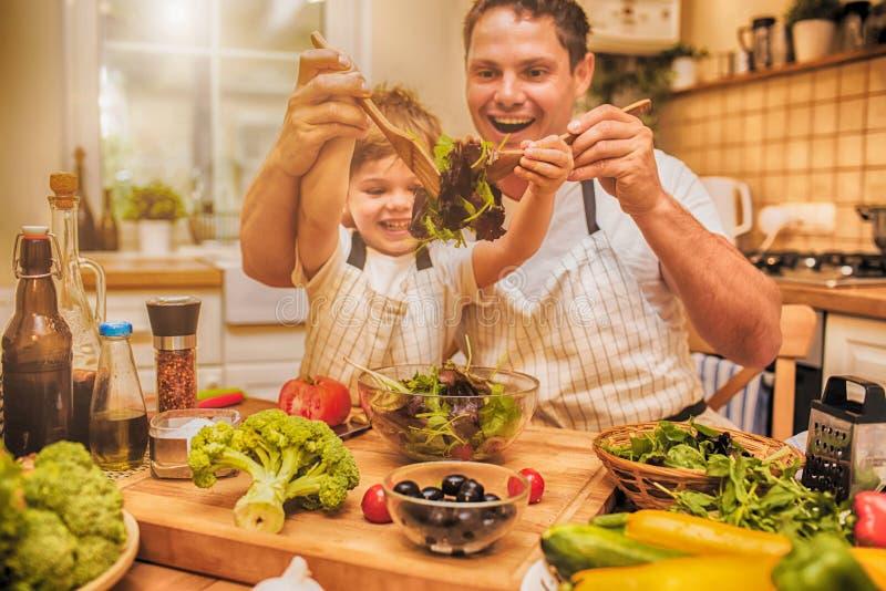 供以人员烹调在有小儿子的厨房 图库摄影