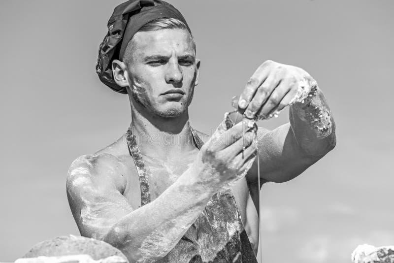 供以人员用面粉工作或厨师盖的肌肉面包师室外,在背景的天空 贝克加鸡蛋准备面团 免版税库存照片