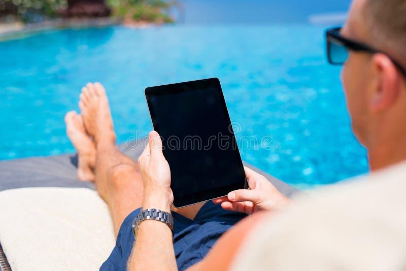 供以人员看片剂计算机,当晒日光浴由水池时 库存照片