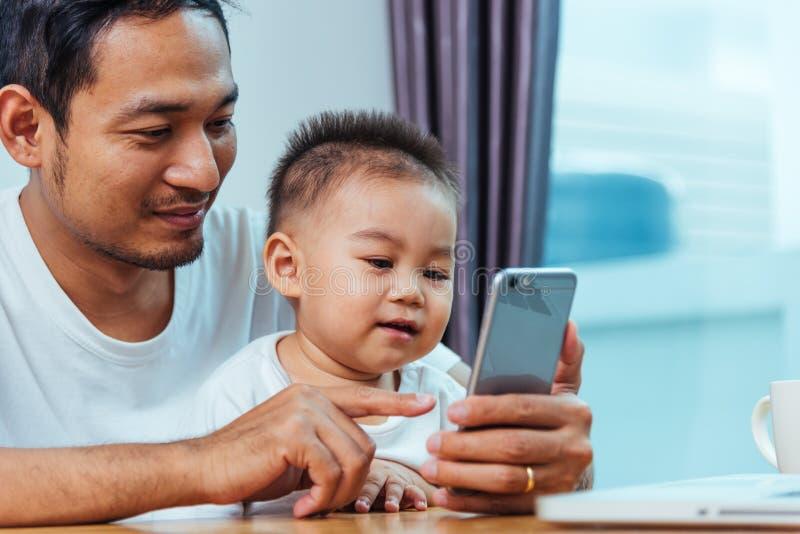 供以人员研究便携式计算机和使用智能手机techn的父亲 免版税图库摄影