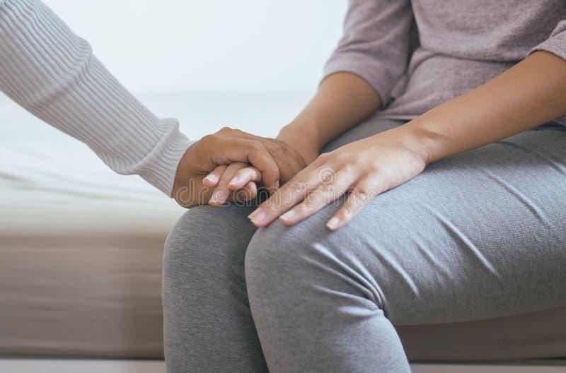 供以人员给手沮丧的妇女,拿着手患者, Meantal医疗保健概念的精神病医生 免版税图库摄影
