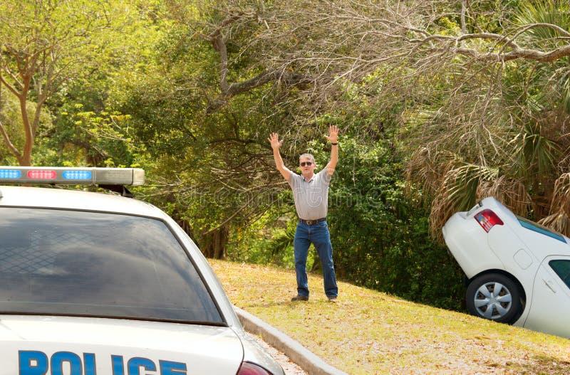 供以人员被击毁的汽车入挥动在警察汽车下的深垄沟 免版税库存图片