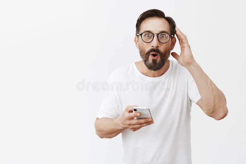 供以人员被留下深刻印象对什么小配件可能做 与胡子的发笑和喜欢的可爱的愉快的男性在玻璃和白色 库存照片