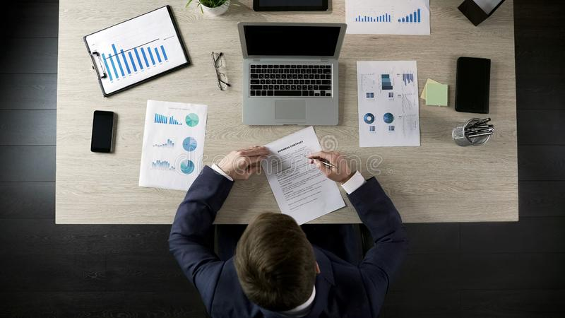 供以人员读书企业合同,达成协议以伙伴,顶视图 免版税库存照片