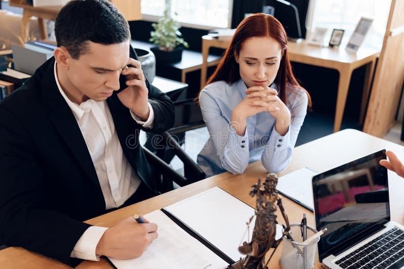 供以人员谁与他的妻子离婚关于电话咨询与律师 生气妇女在谈话的人旁边坐电话 免版税库存图片
