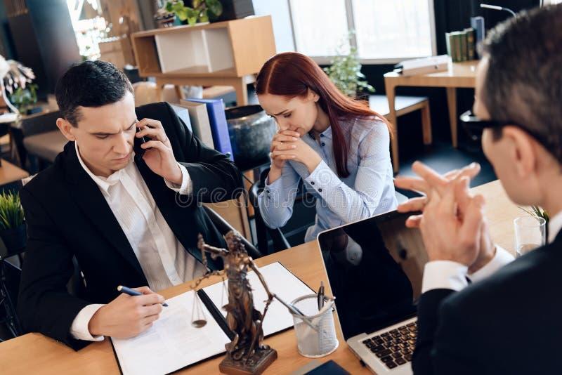 供以人员谁与他的妻子离婚关于电话咨询与律师 生气妇女在谈话的人旁边坐电话 图库摄影