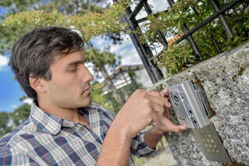 供以人员贴合电子安全设备到外墙 免版税库存图片