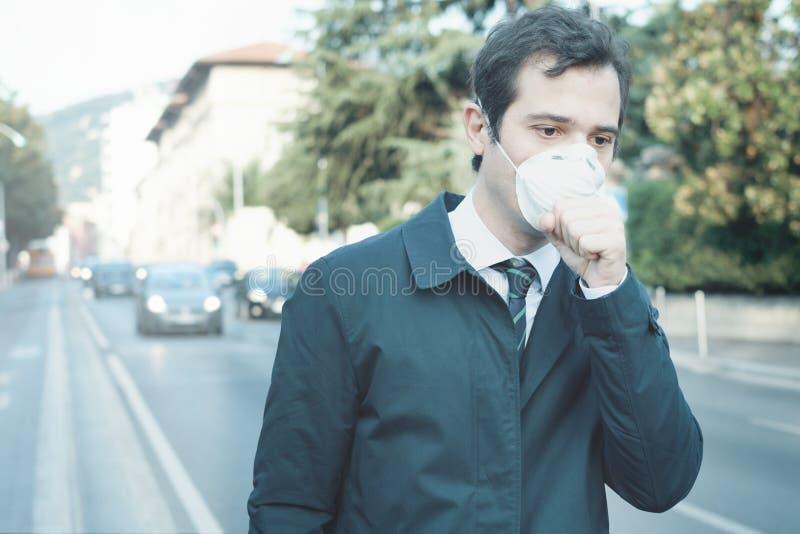 供以人员走在城市佩带的保护面具反对烟雾空气 库存图片