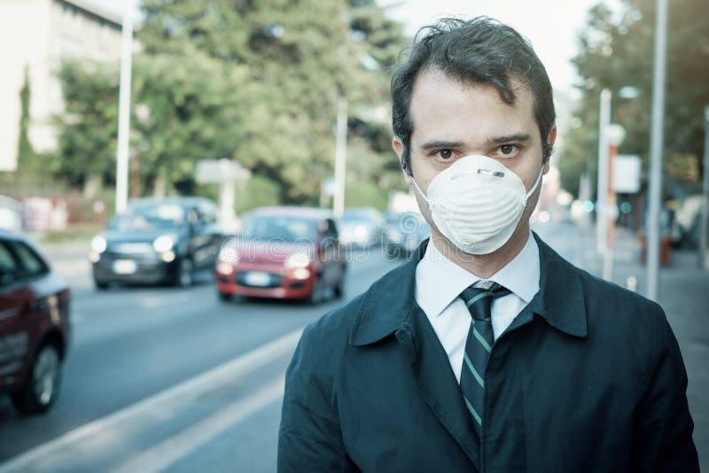 供以人员走在城市佩带的保护面具反对烟雾空气 图库摄影