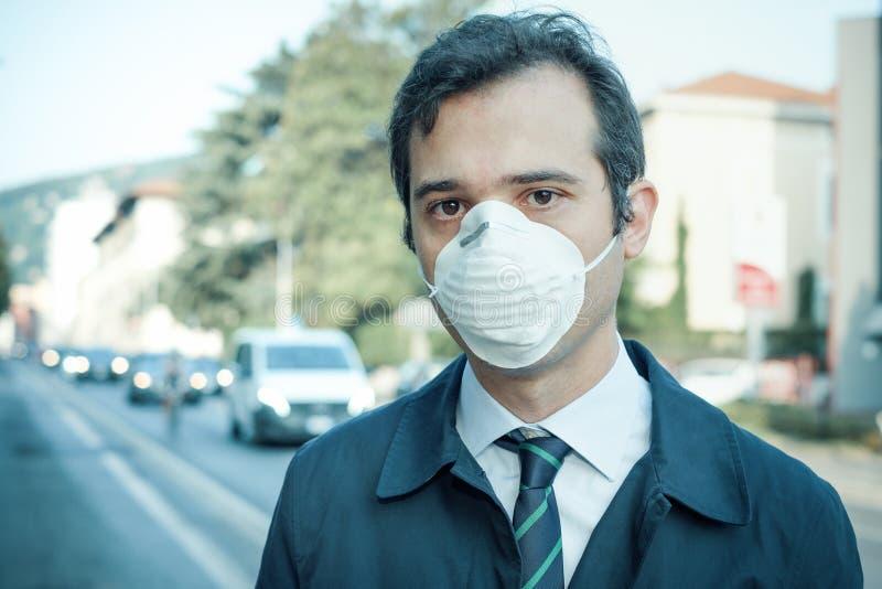 供以人员走在城市佩带的保护面具反对烟雾空气 库存照片