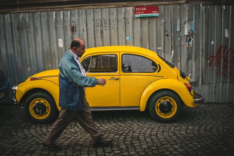 供以人员走由黄色葡萄酒大众kafer在篱芭附近 免版税库存图片
