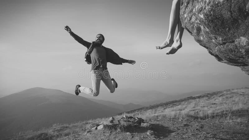 供以人员跳跃在蓝天的山的行家 免版税库存图片