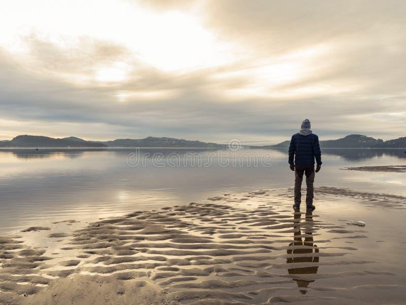 供以人员身分在海滩,人的反射在水中 风平浪静、薄雾和雾 Hamresanden,克里斯蒂安桑 库存图片