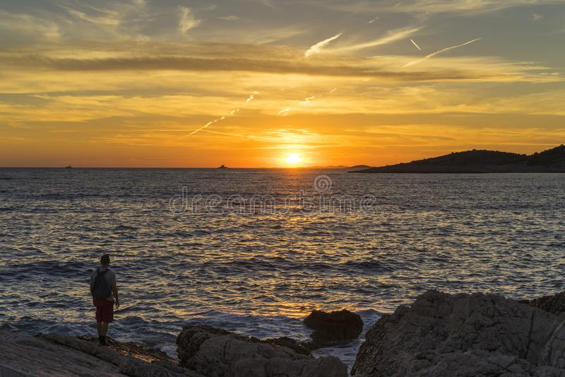 供以人员身分户外在看太阳的海岸去下来在海 免版税库存照片