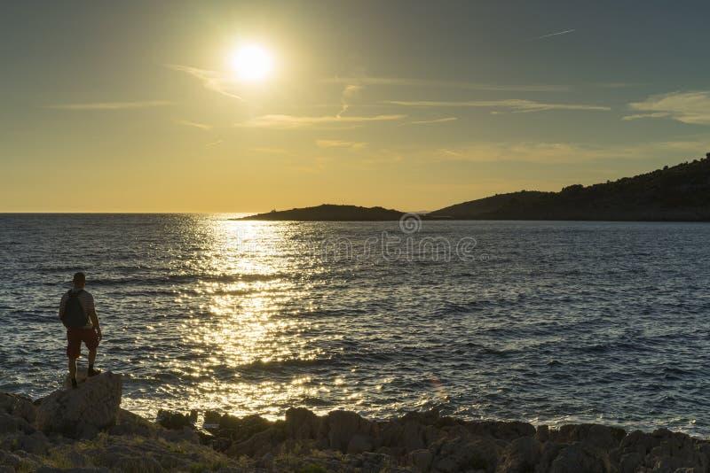 供以人员身分户外在看太阳的海岸去下来在海 库存图片