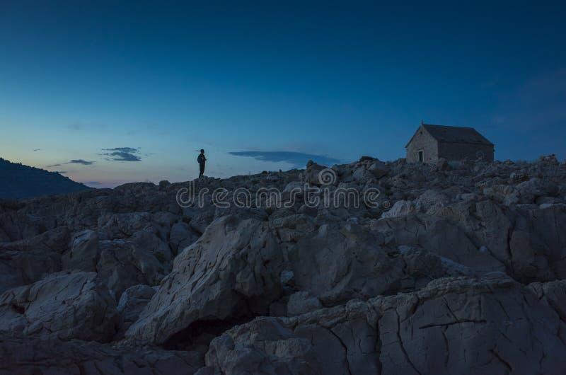 供以人员身分户外在石岩石在小天主教会前面的晚上在Razanj克罗地亚 图库摄影