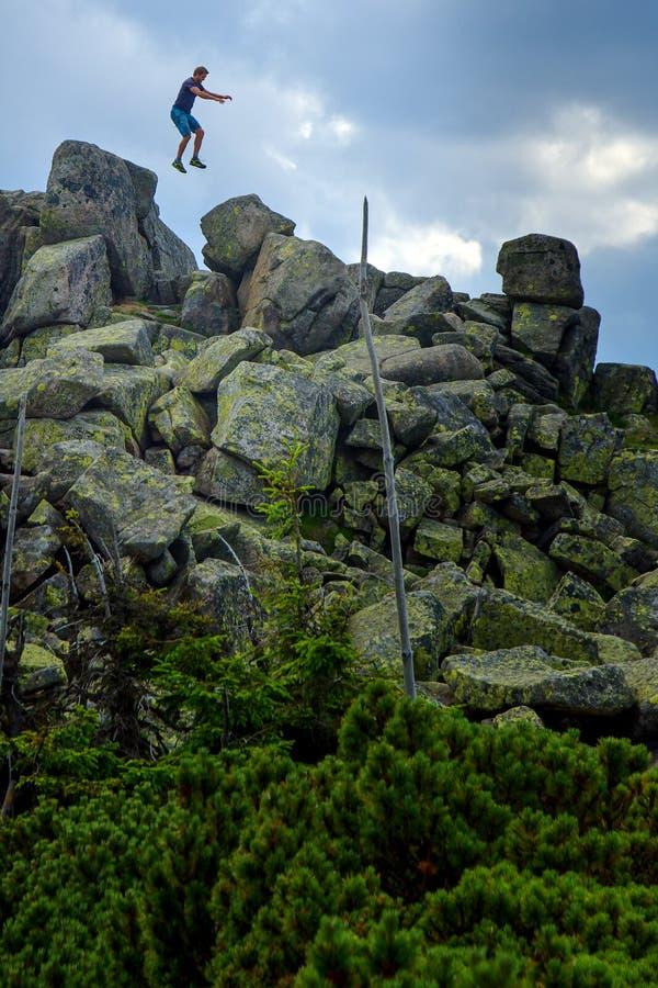 供以人员运动员跳跃在岩层的-男性石头 免版税库存照片