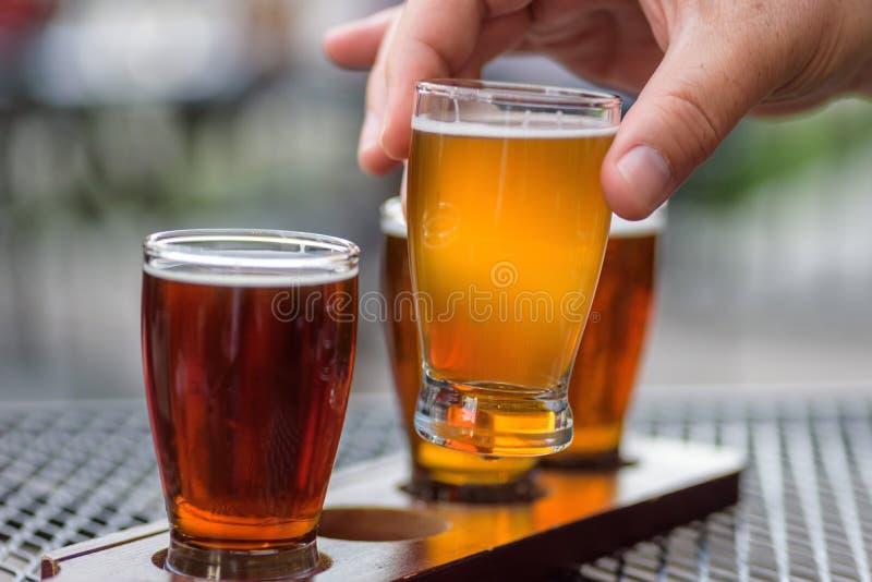 供以人员采样啤酒飞行在一室外taphouse 免版税库存图片