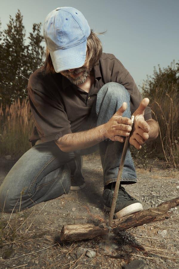 供以人员野营本质上做与木棍子摩擦的火用人工 免版税库存图片