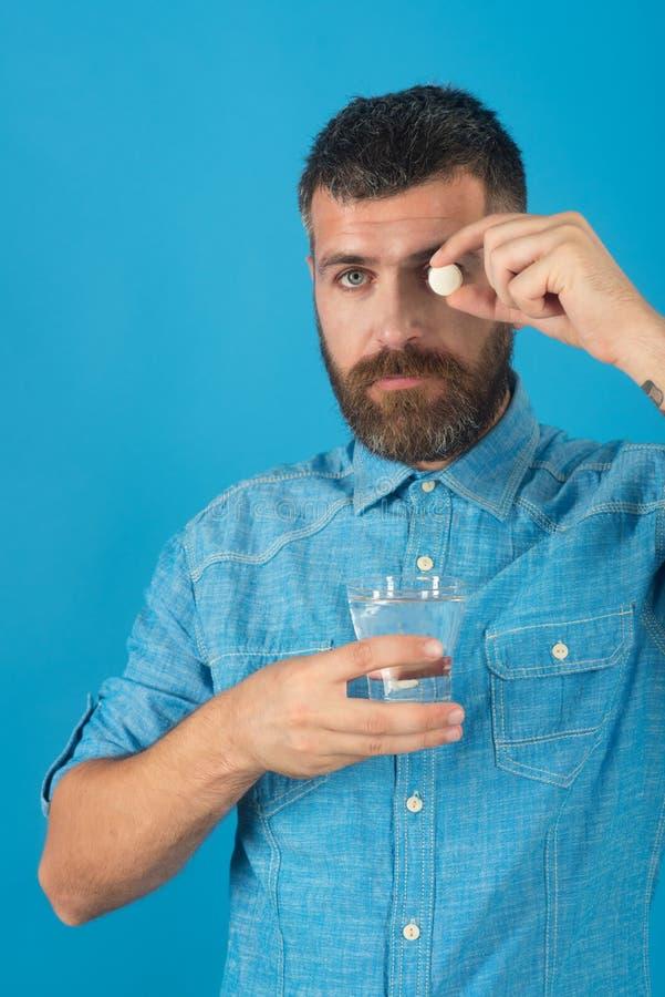 供以人员饮料医疗药片用在蓝色背景,头疼的水 库存图片