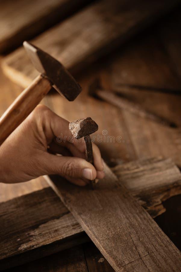 供以人员驾驶在一个木十字架的一个钉子 免版税图库摄影