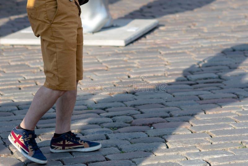 供以人员` s在路面的腿简而言之和运动鞋 免版税库存图片