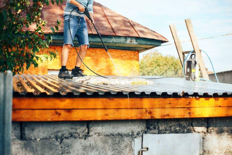 供以人员wach干净的地毯室外在屋顶用水 免版税库存照片
